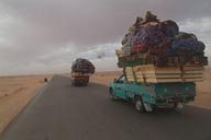 Overloaded pick-up trucks on route to Siva oasis, Harmattan heavy skies.