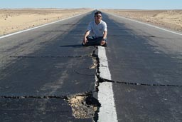 Broken asphalt desert road Egypt.