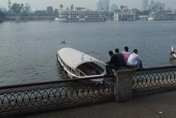 Four men sit on a railing in Cairo, looking out on Nile.