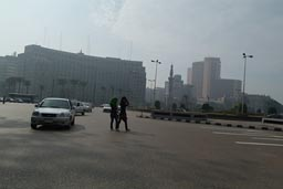 Cairo, street, smog, veilled girls crossing.Tahrir square.