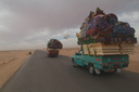 Western Egyptian desert road, pick up trucks fully/over loaded.