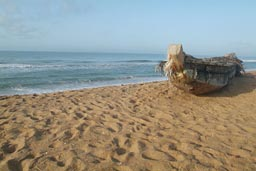 Grand Popo, morning pirogue, fishing boat, sitting on sand. Sea behind
