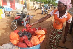 Black girl selling arange goats cheese in Natingou, Benin.