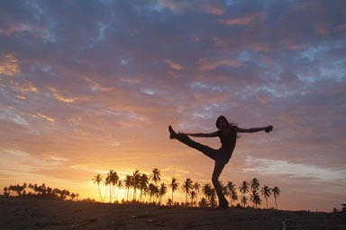 Sunset dance on beach, palm trees in red sky, girl dancing on beach.