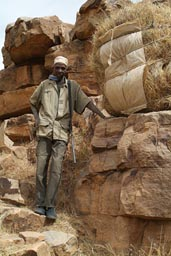 Dogon hunter and rifel, his straw load, on descent from cliffs