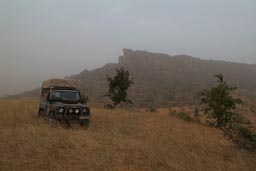Bushcamp Land Rover in front of Dogon falaises/cliffs, Harmattan think sky.