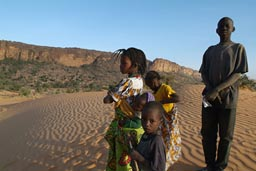 Peul children in Dogon land, on dunes, Cliffs in background.