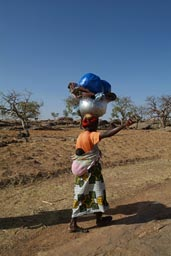 Sanga. Dogon woman, baby on back, carrying heavy head load.