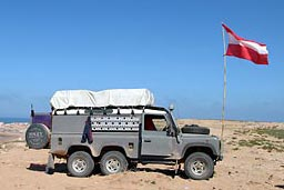 Land Rover Defender 6x6 on Tifnit beach with Austrian flag.
