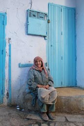 Chefchaouen, alley blue and white, old woman in front of blue door