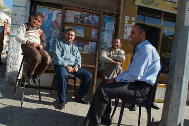 Friendly Syrian men and a boy sitting, laughing in street.