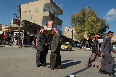 Syrian men wearing the Keffiyeh shake hands in street.