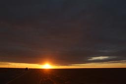 Sun under clouds, Syrian desert, road, car. Before sunset.