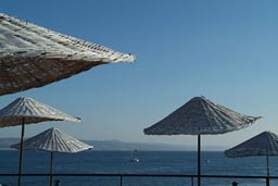 Straw umbrellas, restaurant terrace, Galipoli, Turkey, Dardanelles in back,