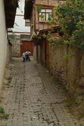 Children on bike play, cobblestone alley Safranbolu.