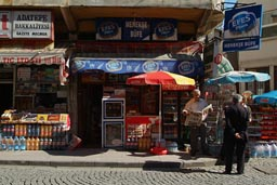 Man reading paper in front of shop. Giresun, Trabzon.