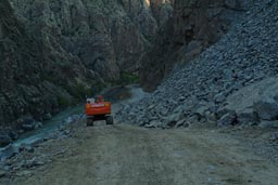Hitachi bulldozer rolls down the river Coruh valley, destruction, Turkey.