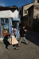 Man, veiled woman, walk past shop, Erzurum, Turkey.