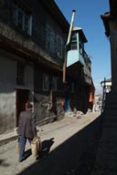 Man walks up sun lit street in Erzurum old district.