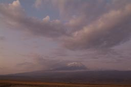 Mount Ararat, dusk, violet colors, haze, a few clouds.