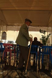 Old man, enters cafe terrace, Mardin, Turkey.
