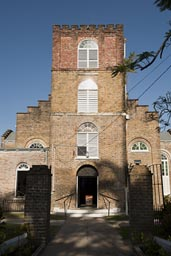 Front of brick St. John's Cathedral in Belize City. A sign on entry says: A contribution is requested from visitors!
