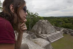 3 relgious temples on top of Canaa. C. is contemplating the greatness of the Caracol pyramid structure in the Maya mountains in Belize.