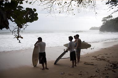 Brazillian surfers watch the waves on lone beach, Caribbean Costa Rica.