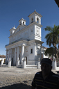 Suchitoto, El Salvador. Shadow/silhuette of man in front of white church and blue sky.