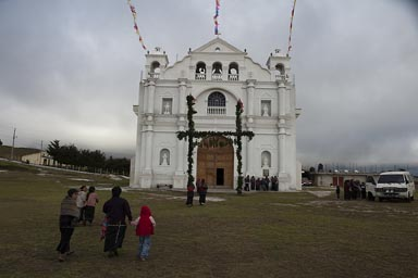 Nueva Santa Catarina Ixtahuacan. Indigenas headed for church. Overcast skies, iglesia in bright white.