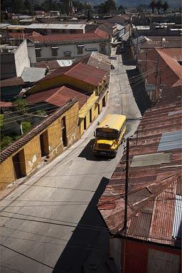 Steep street, rusty tinned roofeed houses, yellow bus, Guatemala. San Marcos, Western Highlands.