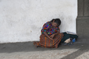 Indigenous lady, Maya, sleeps leaned on house wall, street in Antigua, Guatemala.