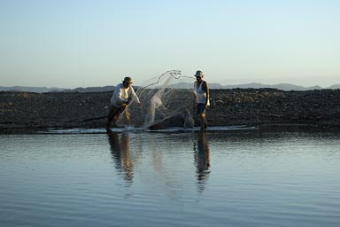 Not so professional Sunday's fishermen from Managua throw their net, El Ostional, Nicaragua.