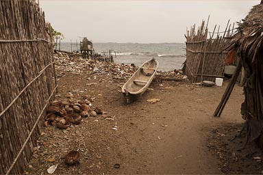 Dugout canoe and trash betwenn shags on beach in Urwargandub, Guna Yala, Panama.