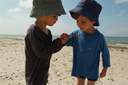 Boys in hats found a bug on beach in Latvia.