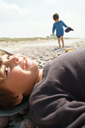 Daniel lies down, smiles, David in back. Beach in Latvia.