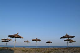 Parasols of straw on beach in Larnaca, Cyprus, Clear blue evening skies.