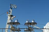 Detail of fishing vessels, lighting. Two birds, blue sky.