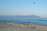 Mount Artos, Chalkidikim seen from Sarti beach on Sithonia, with Football player on Sarti beach.
