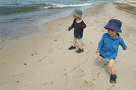 Twins and hats, run on beach, Latvia.