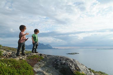 On top of cliff, late sun, boys in Norway.