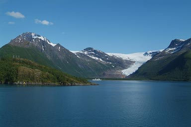 A glacier extends to banks of a fjord, Norway.