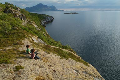 Sitting on soft moss, staring at fjord in late sun.
