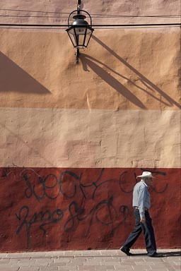 Morelia, a man with hat walks by a colorful house facade.