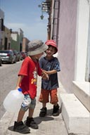 Twin boys laugh and play with a waterbottel in street of Campeche, Mexico. Series of 4 pictures.