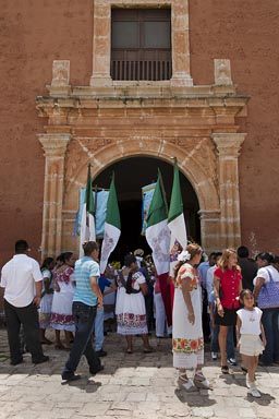 Maxcanu, Sunday. People in traditional white dress and Mexican flags outside church. Yucatan.