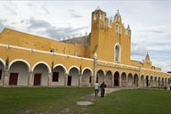 Priest walking accross courtyard/atrium, Izamal, Yucatan.