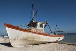 Morning beach in Santa Clara, white and red fishing boat against blue sky.