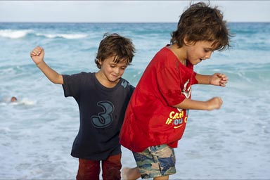 My boys testing the waves in Cancun Beach on evening.