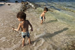 In shallow water in Majuahal, two boys play with a stick.